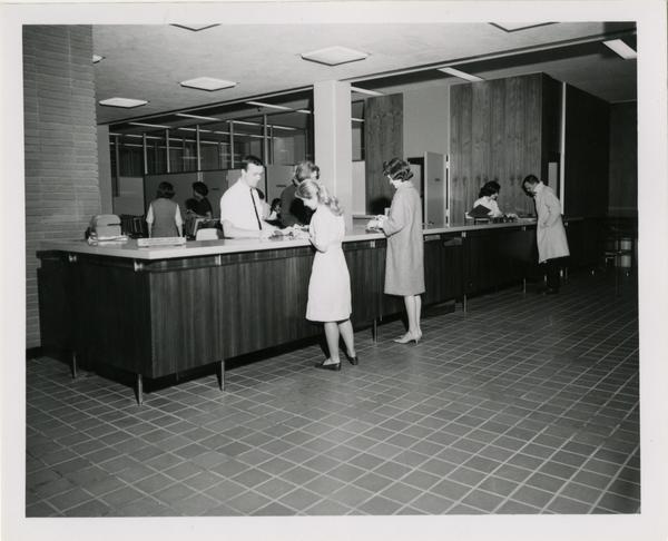 Library employees assisting patrons at circulation desk, ca. 1964