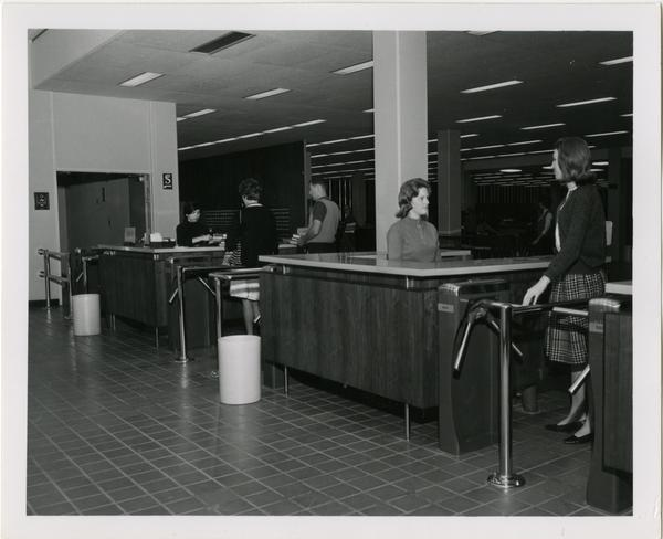 Patrons checking out materials and exiting University Research Library, ca. 1964