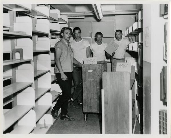 Group of workers pose during the process of loading books on truck for University Research Library move, 1964