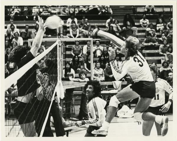 UCLA volleyball team player mid shot during game