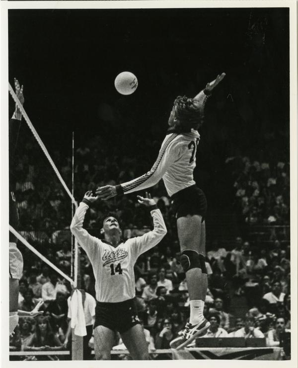 UCLA volleyball team player about to spike the ball during a game
