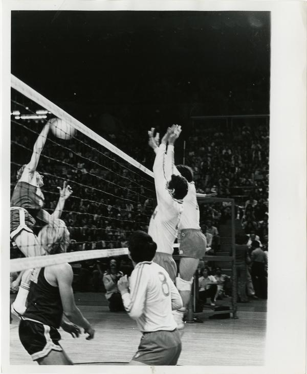 UCLA volleyball player about to spike the ball during a game