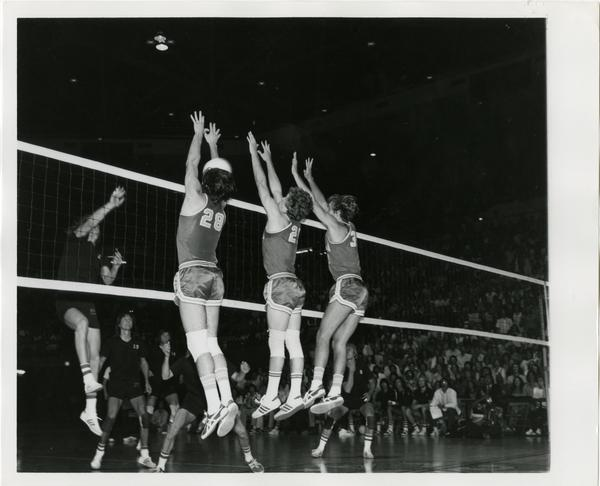 Three UCLA volleyball players attempting to block the ball in front of the net during a game