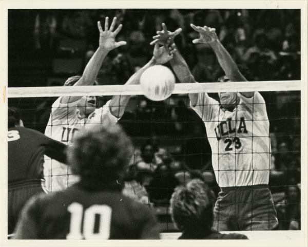 Two UCLA volleyball players attempting to block the ball during a game