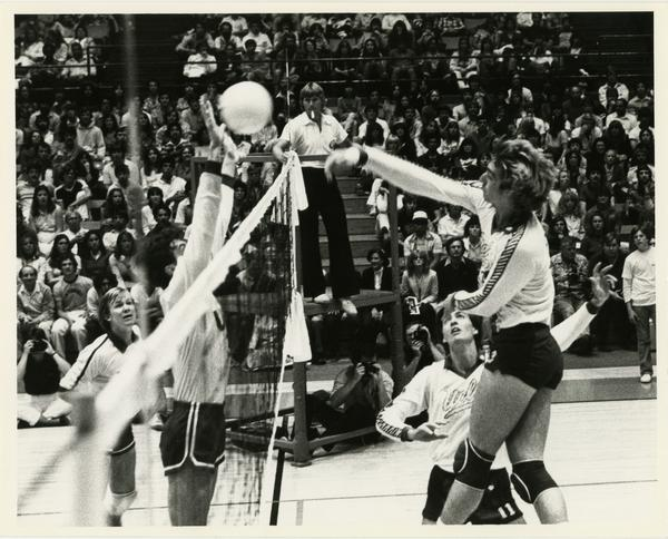 UCLA volleyball player spiking the ball over the net during a game