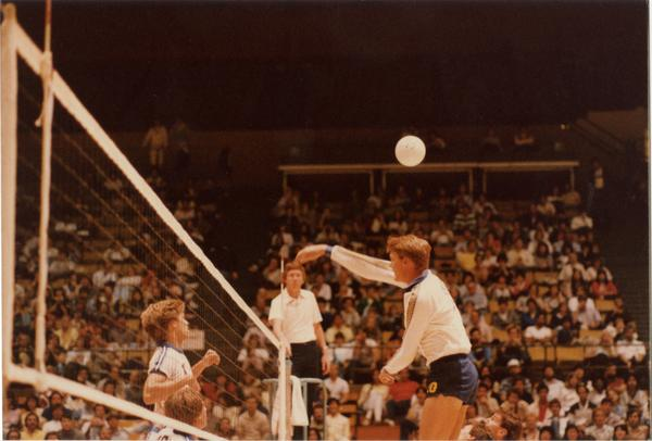 UCLA volleyball player hitting the ball over the net during a game, 1983