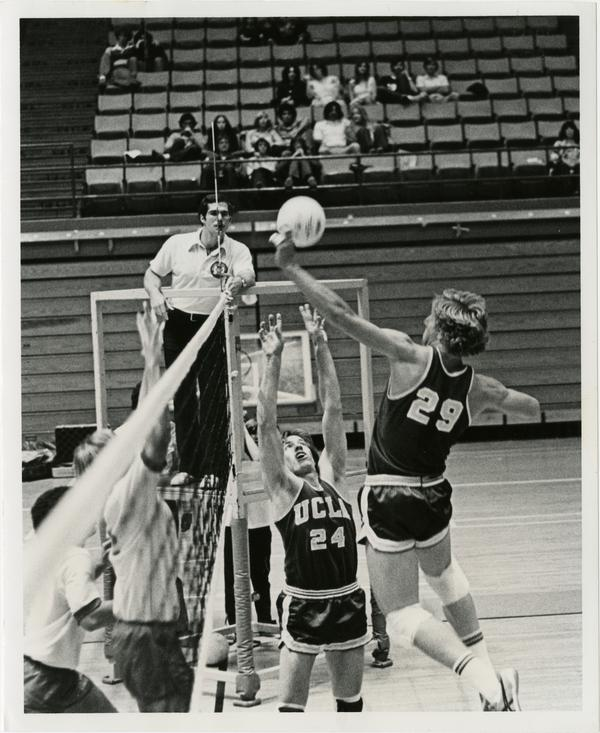 UCLA volleyball player setting the ball for teammate during a game