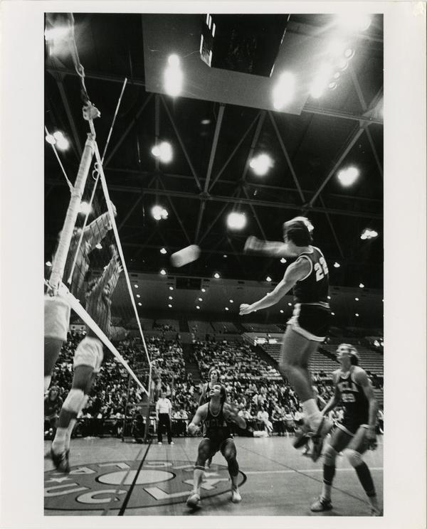 UCLA volleyball player spiking the ball over the net at a game