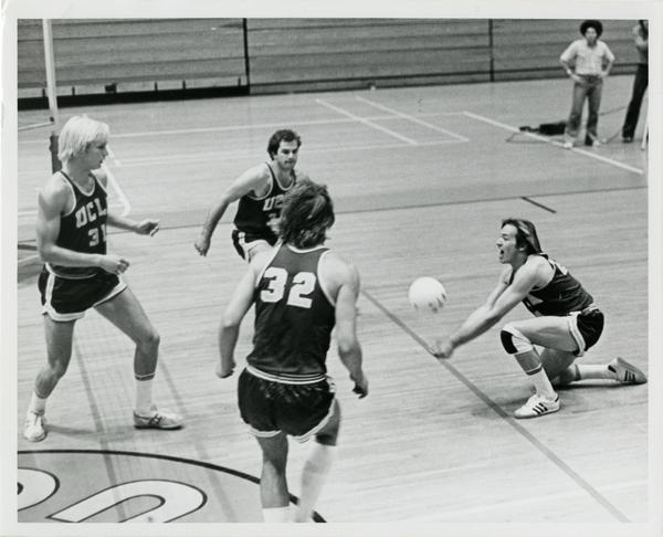 UCLA volleyball player hitting the ball as teammates look on during a game