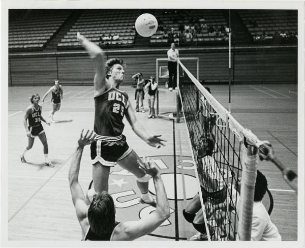 UCLA volleyball player about to spike the ball over the net during a game
