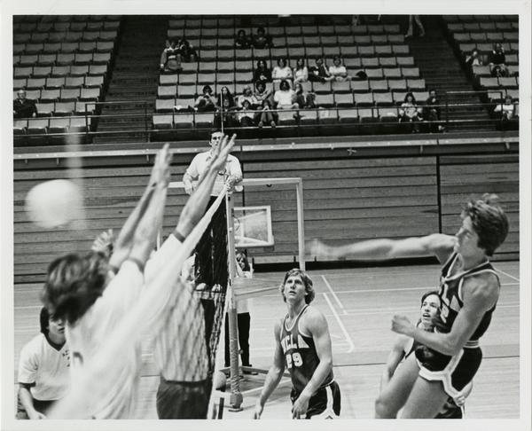 UCLA volleyball player spiking the ball over the net during a game with members of opposing team attempting to block during a game