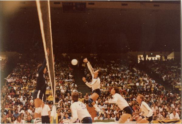 UCLA volleyball player spiking the ball over the net at a game, 1983