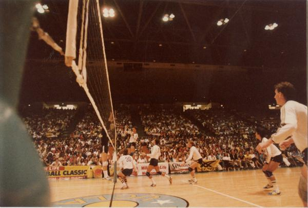 UCLA volleyball player after spiking the ball over the net during a game, 1983
