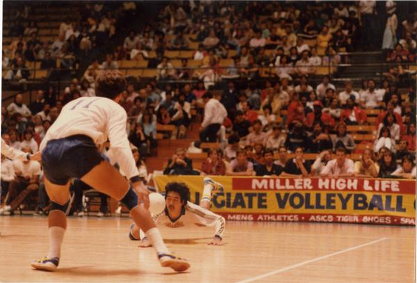 UCLA volleyball player diving for the ball during a game, 1983