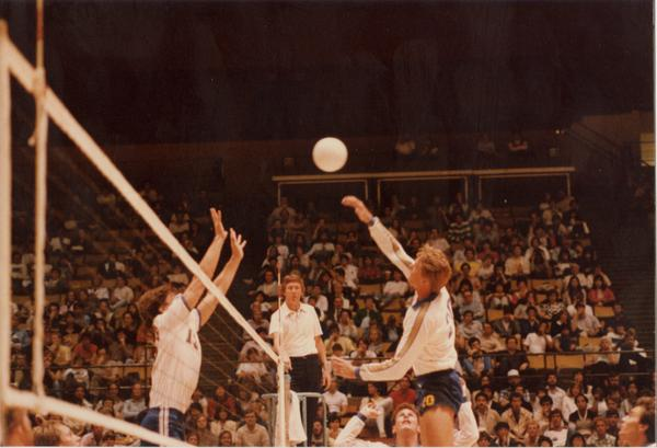 UCLA volleyball player about to hit the ball during a game as opposing teammembers attempt to block, 1983