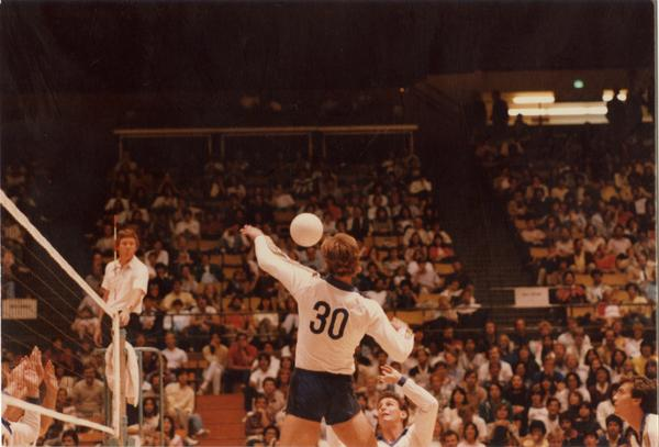 UCLA volleyball player setting the ball for teammate during a game, 1983