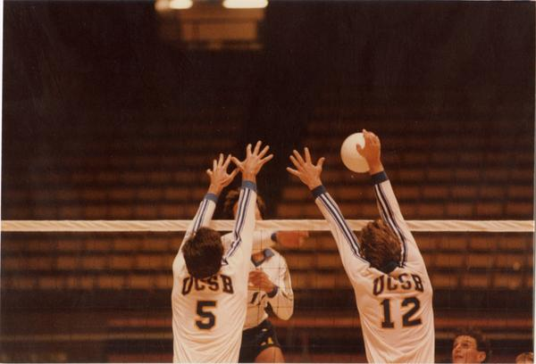 UCLA volleyball player hitting the ball over the net with opposing teammembers attempting to block during a game, 1983
