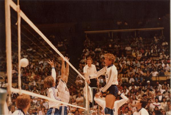 UCLA volleyball player spiking the ball over the net during a game, 1983