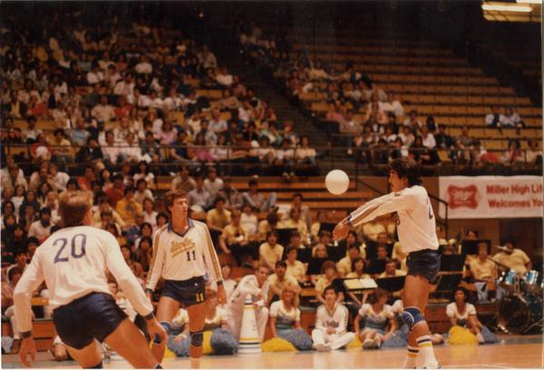 UCLA volleyball player hitting the ball surrounded by teammates during game, 1983