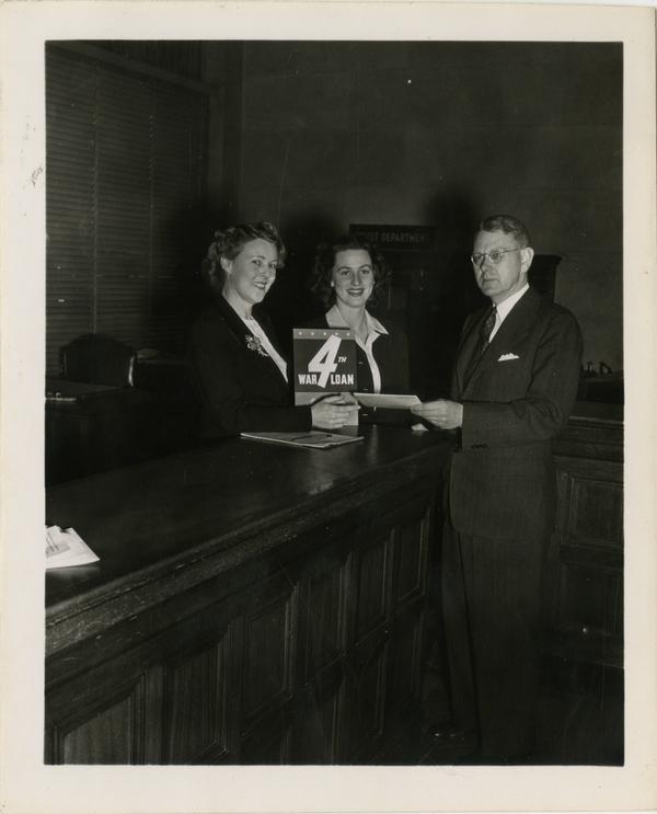 Woman handing war loan to Robert H. Underhill