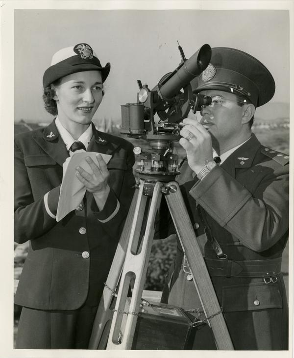 Wave Ensign Helen Alber and Capt. Luis Maria Riviere of the Argentine Air Force take a reading on a theodolite, an instrument used for checking the flight of weather ballons