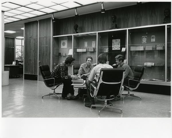 Jean Aroeste and students sitting in Special Collections Exhibit area in front of display cases