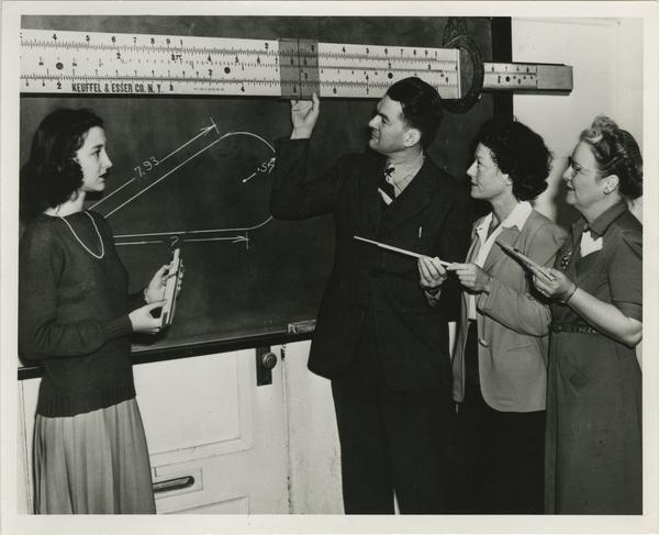 Students and professor working with slide ruler on blackboard