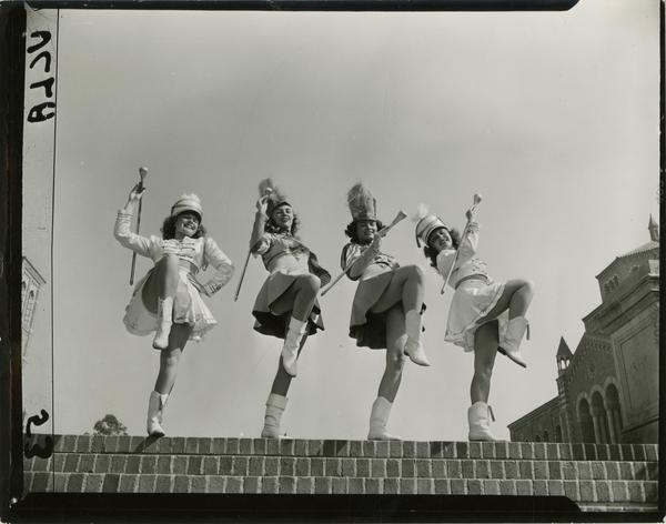 Contact print of four majorettes posing with batons at the top of the Janss Steps, ca. 1940's
