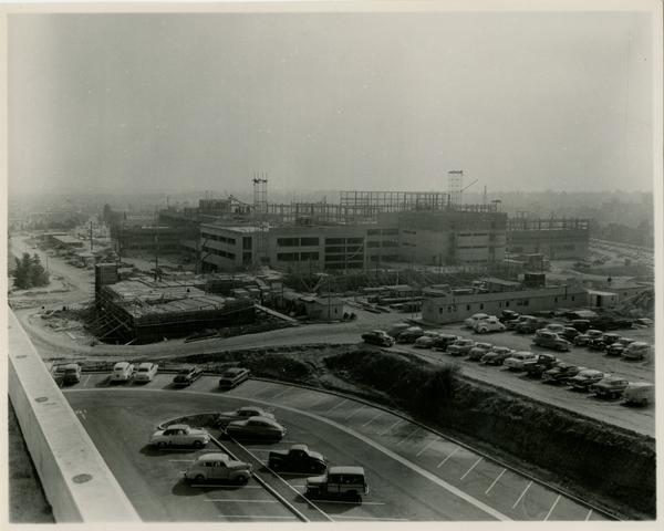 UCLA medical center after more construction has occurred with the surrounding parking lot with cars in it, c. 1951