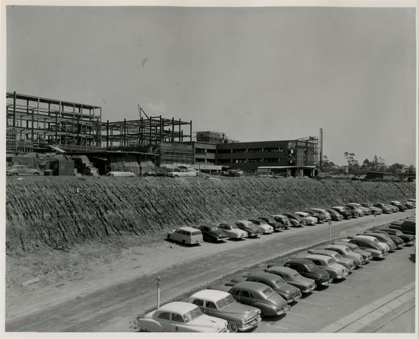 Construction sign for the UCLA medical center with cars parking in the dirt, c. 1951