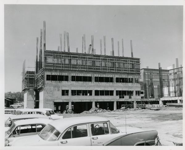 Medical Center during construction with cars parked nearby, 1959