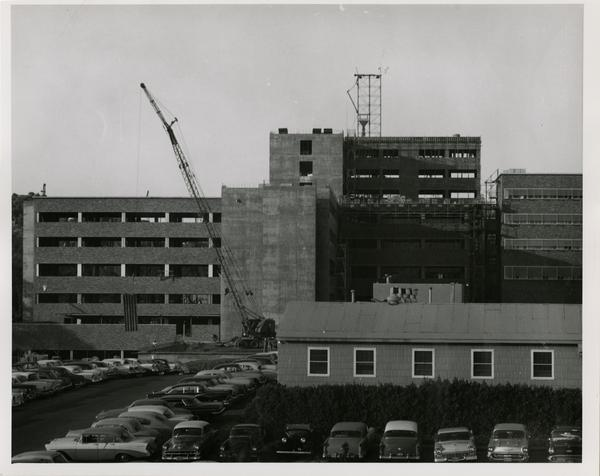 UCLA medical center closer to the finishing of construction with cars parked in the parking lot, 1959