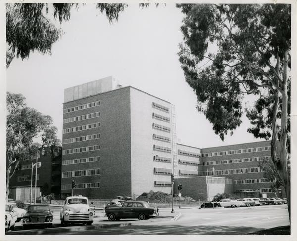A finished UCLA medical center with a parking lot full of cars, 1960