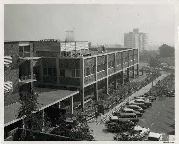 A completed UCLA medical center with cars parked in the street out front, 1962