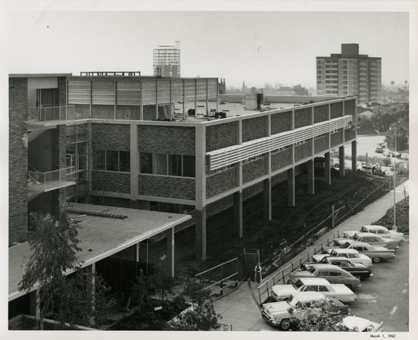 A completed UCLA medical center with parks parked in the street out front, 1962