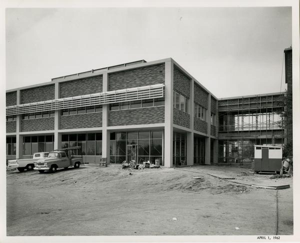 Part of the UCLA medical center close to completion, still standing on dirt and with work trucks parked around it, 1962