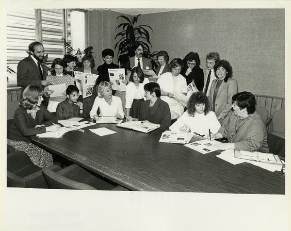 Medi-sence editorial board examine printed publications for a group photo, February 1985