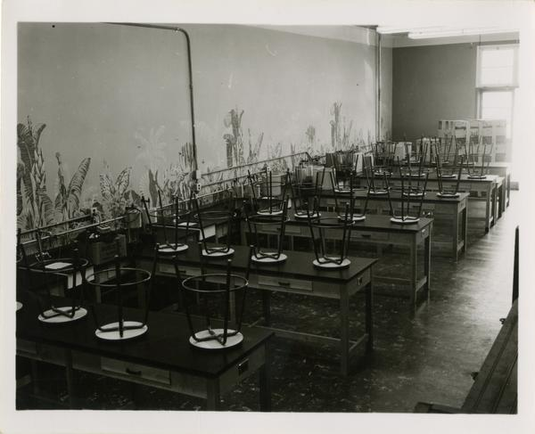 Medical school classroom with empty tables with stools turned upside down on them, 1955