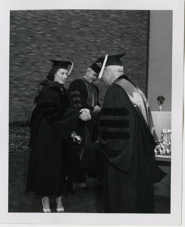 Medical school student shakes hands with the academic procession while receiving her diploma at graduation, 1956