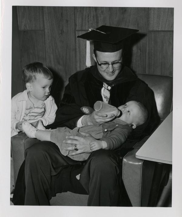 Graduate of the medical school feeds his child as another child looks on after the ceremony, 1956