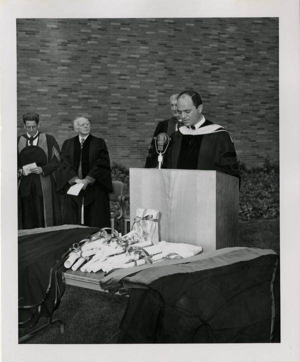 Member of the academic procession addresses the crowd at the graduation, 1956