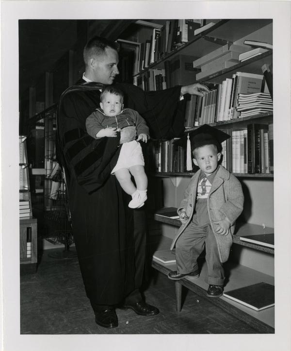 Graduate student of the medical school holding his child while his other child wears his graduation cap in the library after the ceremony, 1956