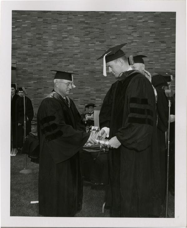 Graduate student receives his diploma from the academic procession during the ceremony, 1956