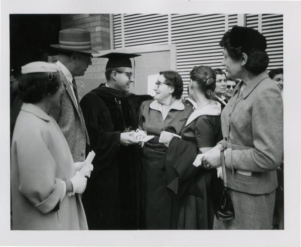 Graduate student of the medical school greets his family after the ceremony, 1956