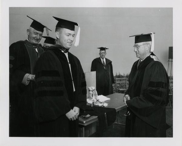 Graduate student accepts his diploma at the ceremony, 1956