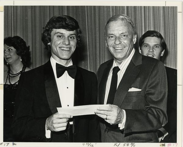 Frank Sinatra and an opera student holding an announcement card at an award ceremony