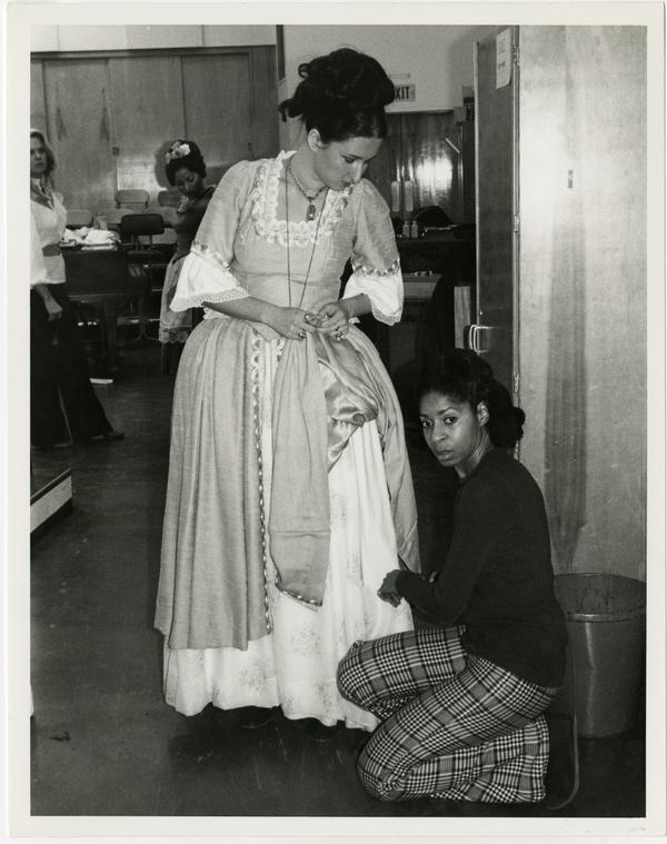 A woman assists an actor with her costume in preparation for Cosi Fan Tutti Opera, 1978