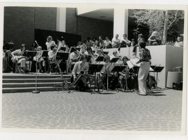 Conductor with his back turned, leading the jazz ensemble in a performance outside