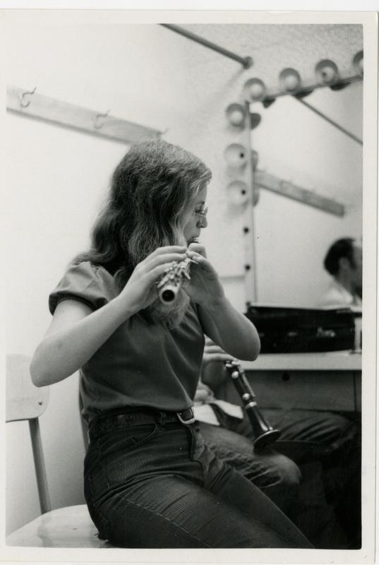 Member of the Jazz Ensemble playing the flue with a clarinet resting on her knee during a practice
