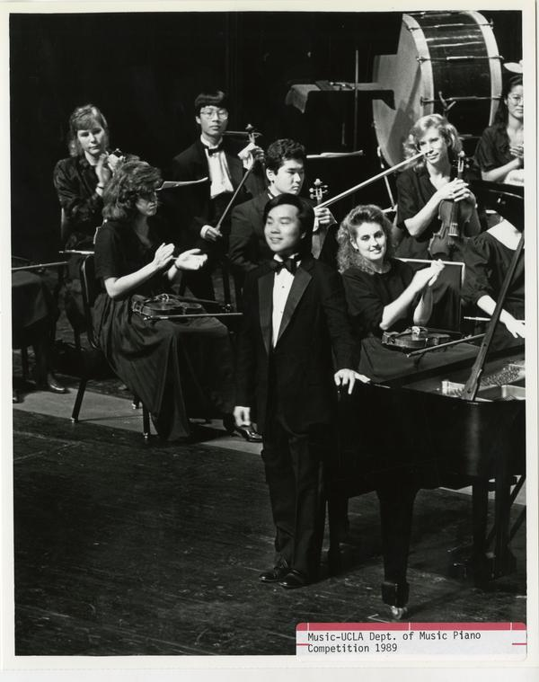 Unidentified student stands up next to his piano with other musicians in the background during the Department of Music Piano Competition, 1989